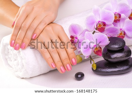 beautiful manicure with pink orchid and towel - stock photo