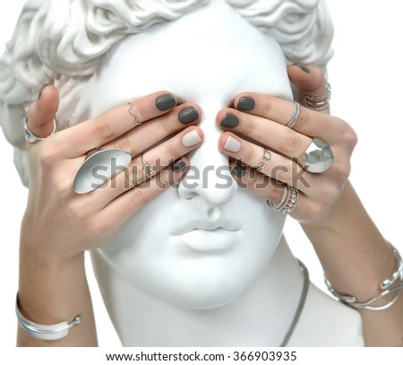 Beautiful manicure woman hands covering the eyes of an apollo statue on a white background - stock photo