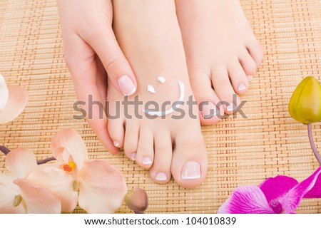 Beautiful manicured feet with pedicures and flowers. Close-up - stock photo