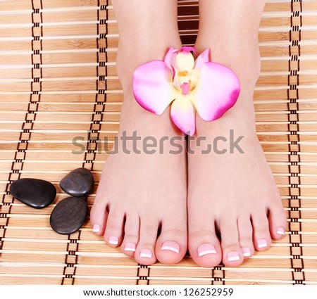 beautiful manicured female bare feet with orchid flowers and spa stones over bamboo mat, pedicure, foot care feet care, spa - stock photo