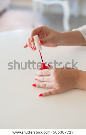Beautiful manicured woman's nail with red nail polish on the coffee shop background