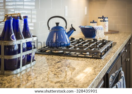 Beautiful Marble Kitchen Counter and Stove With Cobalt Blue Decor. - stock photo