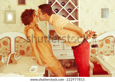 Beautiful married couple of hipsters in trendy clothing kissing and smiling in vintage cafe with white furniture. Vintage design and accessories. Man with lantern. Wedding day. Daylight. Indoor shot - stock photo