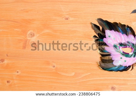 beautiful mask of feathers on a yellow board - stock photo
