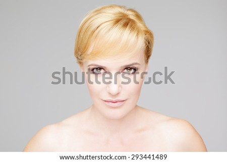 Beautiful mature blonde healthy woman the head shut portrait on gray background