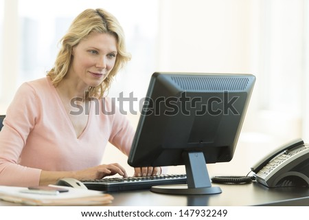 Beautiful mature businesswoman using computer in office - stock photo