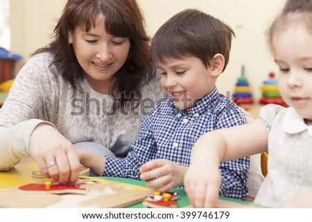 beautiful mature caucasian female teacher collects the puzzle with a pupil,  a boy of preschool age. In the classroom, at the green table. - stock photo