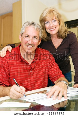 Beautiful mature couple going over bills together and smiling. - stock photo