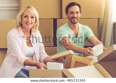 Beautiful mature couple in casual clothes is packing their stuff, looking at camera and smiling while sitting on the floor among boxes, moving to the new apartment