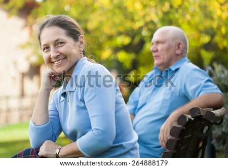 beautiful mature couple sitting on   bench in autumn park. - stock photo
