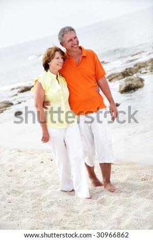 beautiful mature couple walking along the beach - stock photo