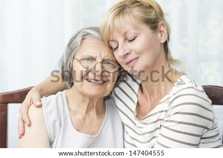 Beautiful mature daughter with closed eyes hugging her senior mother. - stock photo