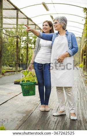 Beautiful mature florist helping a female customer to choose plants - stock photo