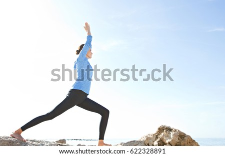 Beautiful mature healthy woman practicing yoga, stretching body against a blue sky on nature rocks beach, sunny outdoors. Wellness, fitness, sport and well being lifestyle, positive mind, exterior.