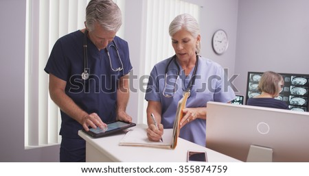 Beautiful mature nurse writing notes in patient file with male colleague - stock photo