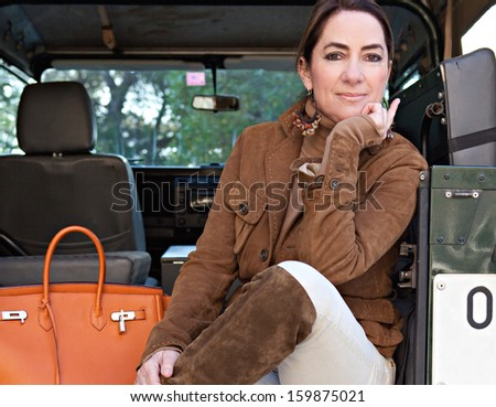 Beautiful mature tourist woman sitting at the back of a four wheel drive car at a safari park ready for adventure and wearing a jacket and boots during a sunny day outdoors.