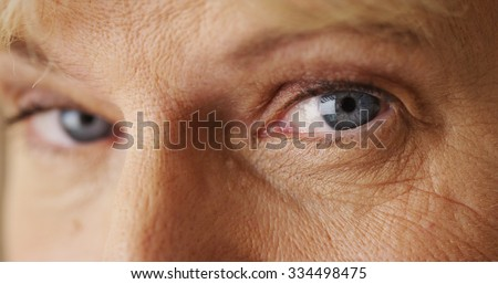 Beautiful mature woman blue eyes closeup - stock photo