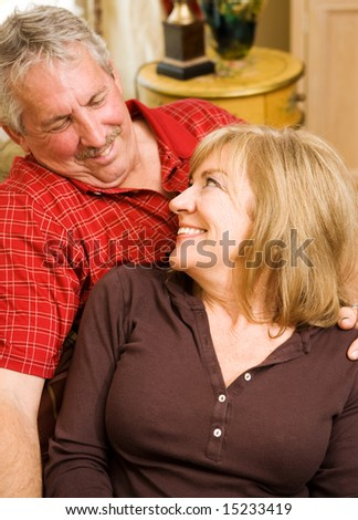 Beautiful mature woman gazes lovingly into the eyes of her handsome husband.  Focus on the wife. Vertical view. - stock photo