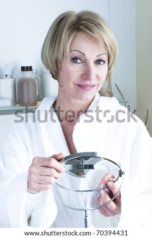 Beautiful mature woman holding mirror - stock photo