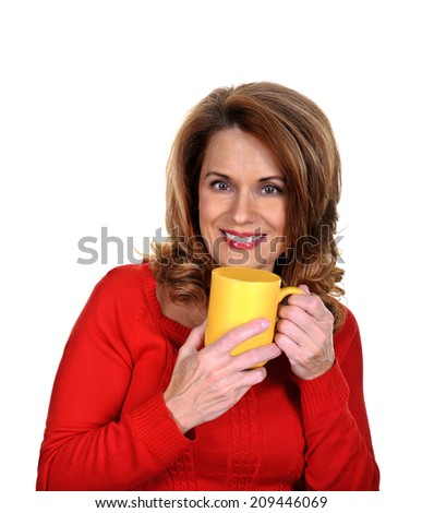 Beautiful Mature Woman in a Red Sweater holding a Yellow Coffee Cup - stock photo