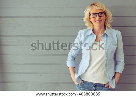 Beautiful mature woman in casual clothes and eyeglasses is looking at camera and smiling, standing against gray background - stock photo