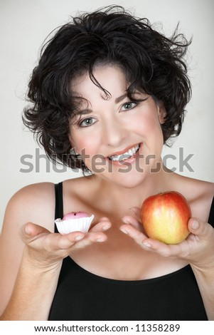 Beautiful mature woman in her late 30s early 40s choosing between an apple and a cake - stock photo