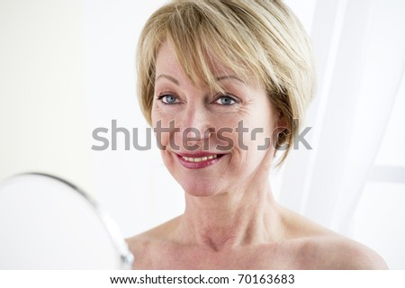 Beautiful mature woman making up - stock photo