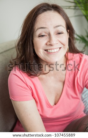Beautiful mature woman relaxing in the couch smiles with goofy face straight at camera