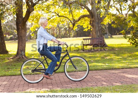 beautiful mature woman riding a bike at the park - stock photo