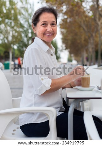 Beautiful mature woman sitting at  table in  cafe on  street.