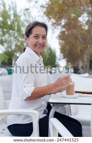 Beautiful mature woman sitting at  table in  cafe on  street.  - stock photo