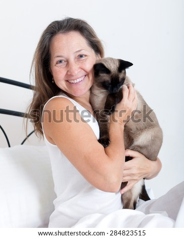Beautiful mature woman sitting on   bed with her cat.  - stock photo