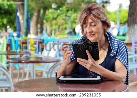 Beautiful mature woman sitting on the sidewalk holding a smart phone and reading a message.. - stock photo