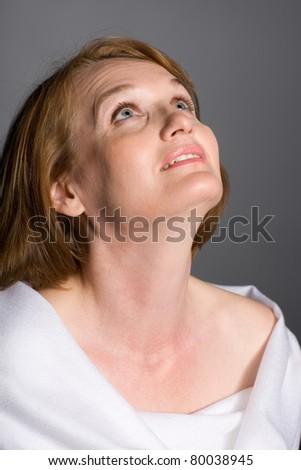 Beautiful mature woman smiling looking up. - stock photo