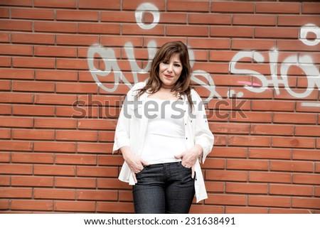 Beautiful mature woman standing brick wall in an urban environment.  - stock photo