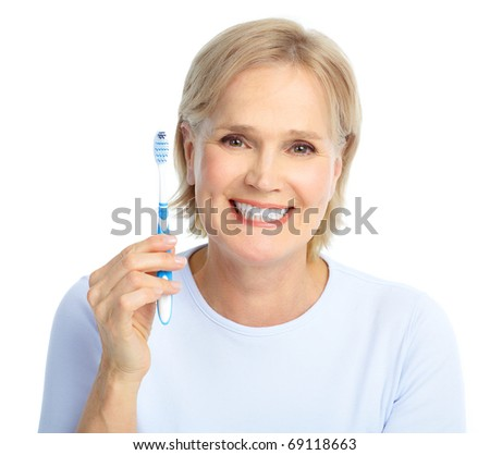 Beautiful mature woman with a toothbrush. - stock photo