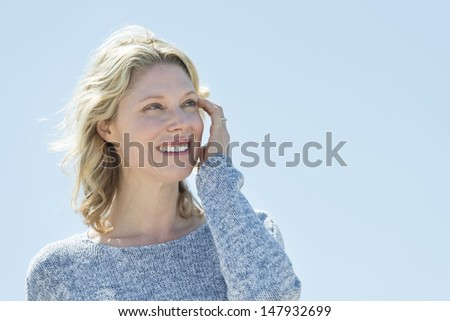 Beautiful mature woman with hand in hair looking away against clear sky - stock photo