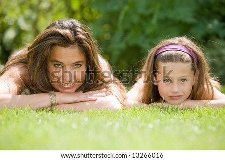 Beautiful mature woman with her 7 year old daughter lying in the grass on a summer day - stock photo