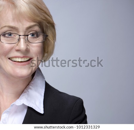 Beautiful Matured Woman happy cheerful caucasian in glasses toothy smile blond studio shot looking off camera. copy space . Grey background. Businesswoman in suit