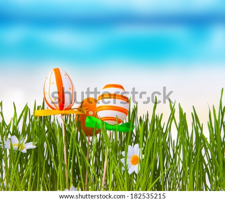 Beautiful meadow and easter eggs with blue sky. Easter concept. Fresh green grass. Color easter eggs.