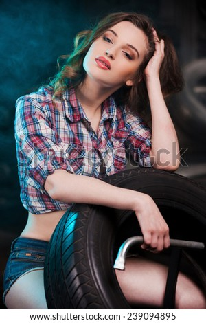Beautiful mechanic. Beautiful young woman leaning at the car tire and looking at camera while sitting in auto repair shop - stock photo