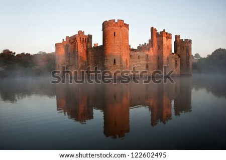 Beautiful medieval castle and moat at sunrise with mist over moat and sunlight behind castle - stock photo