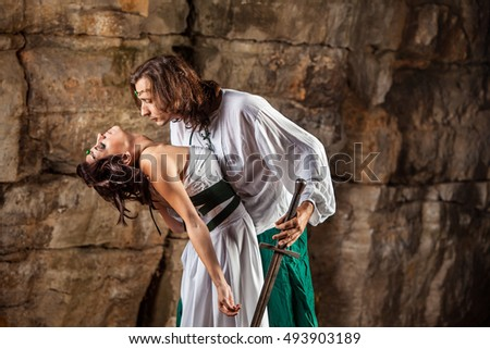 Beautiful medieval couple is kissing on the rocks background.