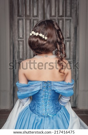 Beautiful medieval woman in blue dress, back - stock photo