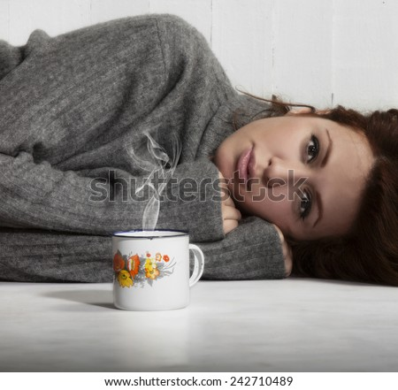 Beautiful melancholic girl lying on the floor with cup of coffee, hot chocolate or tea. - stock photo