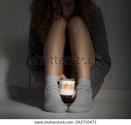 Beautiful melancholic girl sitting on the floor with cup of coffee, hot chocolate or tea. - stock photo