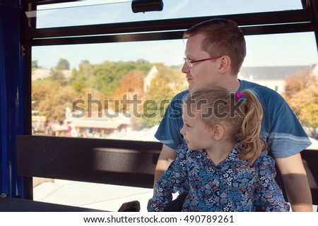 Beautiful men with his pretty happy daughter sitting in ferris wheel cabin at oktoberfest festival