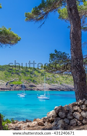 Beautiful Menorca island cove with yachts floating on turquoise water, Balearic islands, Spain - stock photo