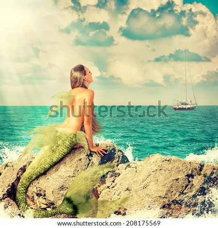 Beautiful Mermaid with fish tail sitting on rocks and looks at a ship on the horizon - stock photo