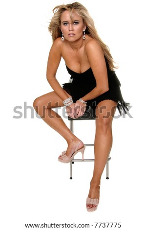 Beautiful mid adult blonde in a strapless black dress sitting on a stool Full body